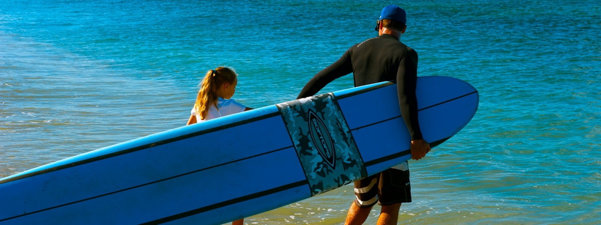 SSM Encourages All Newcomers To Join The Fun:  Here Nichole,  Who Is 9 Years Old And Autistic, Enters The Water With Brian For Her First Surfing Lesson.